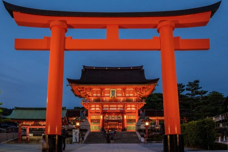 A massive torii gate, lit up at night, in Fushimi-Inari, Kyoto, Japan.
