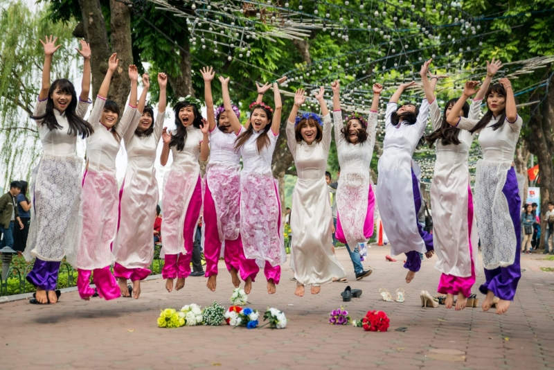 Newly graduated girls jump for joy, in Hanoi, Vietnam.
