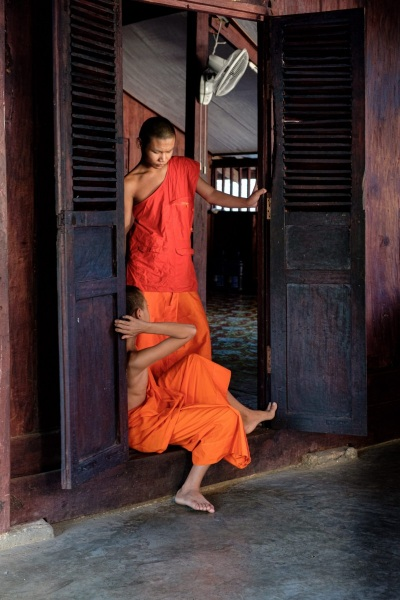 Two novice monks take a break from the heat in Luang Prabang, Laos.