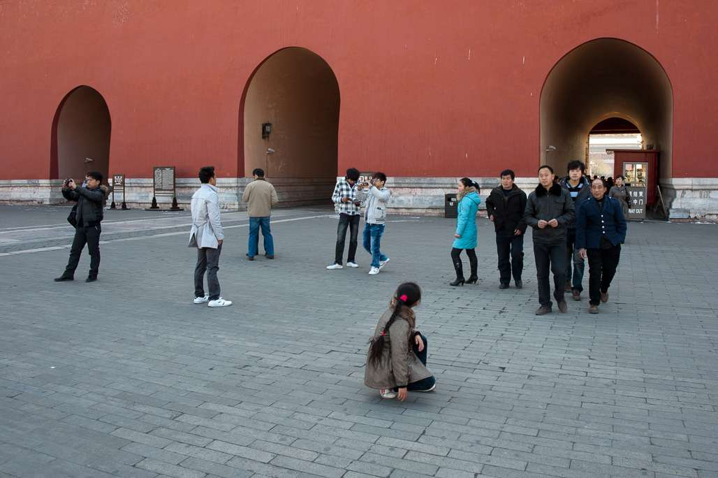 A photo of a crouching girl looking back at the walls of the Forbidden City in Beijing, China.