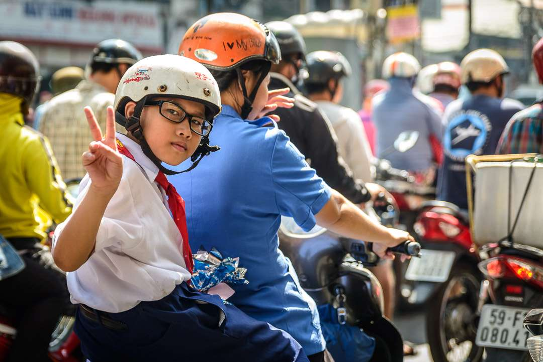 A photo of a student on the back of a motorbike, on her way to school in Vietnam.