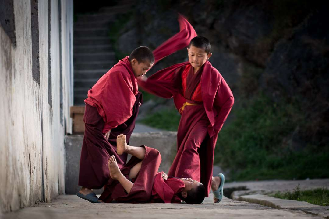 A photo of 3 young monks, playfully establishing hierarchy at the monastery.