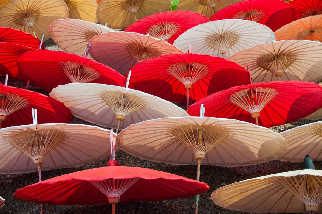 A photo of red and white umbrellas drying in the sun, in Bo Sang, Thailand.